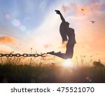 Small photo of Forgive and freedom concept: Silhouette of a woman jumping and broken chains at sunset meadow with her hands raised.