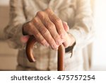 old man hands on walking stick | Shutterstock . vector #475757254