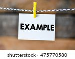 Small photo of Example.Example on paper hanging on the clothesline. On old wood background