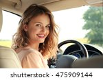 pretty young woman driving car | Shutterstock . vector #475909144