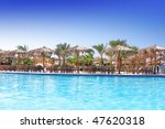 Beauty landscape of sun umbrella, make of reed , beach bed  and water pool. - stock photo