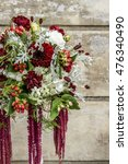 Small photo of Modern wedding bouquet with amaranthus plant, red dahlias, hypericum, carnation and astrantia flowers.