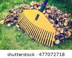 pile of fall leaves with rake... | Shutterstock . vector #477072718