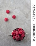 Small photo of Red ripe raspberries in a tiny vintage pewter bowl. Gray background