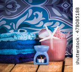 Small photo of Set towels in blue colors with shells, wisp of bast and candle on the background of wallpaper with big pattern
