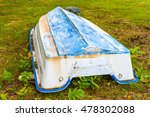 Small photo of Upside down boat on land. The boat has blue keel and yellowing white sides. Dry leaves have started to accumulate around it.