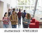 Stock photo students holding tablets and phone talk in university lobby 478513810