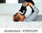 Stock photo  years old pre teen girl lying down on sofa and playing with black kitten 478531249