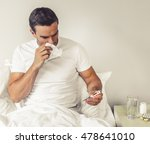Small photo of Handsome man affected by common cold is looking at the thermometer and wiping nose with paper tissue while sitting in bed at home