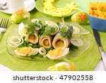 rollmops with gherkins on fish shape plate for easter - stock photo
