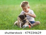 Stock photo cute boy with pug dog on green grass 479234629
