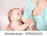a young woman breast feeding a... | Shutterstock . vector #479442310