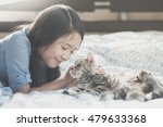 Stock photo beautiful asian girl playing with american short hair cat on the bed 479633368