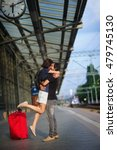 Small photo of Loving couple snog on the platform under the clock. The young man lifted the girl and kisses her. Next to them, a large red suitcase. In the distance, the approaching train.
