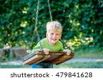Small photo of Thoughtful 5-year-old boy riding on a swing outside. Child having fun in summer.
