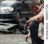 Small photo of Young bleeding man sitting depressed after car accident