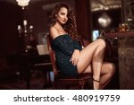 Stock photo beauty young brunette woman sitting at the bar with glass of whiskey in luxury interior 480919759