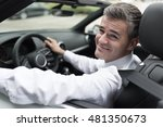 Successful confident businessman driving to work with his brand new expensive car, he is smiling at camera - stock photo