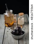 Small photo of Ripe plums in a vintage pewter bowl and ice tea in a glass jug. Weathered wood table