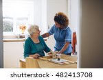 Care Worker Giving An Old Lady...