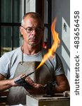 Small photo of Adult male goldsmith check the blowtorch flame for melting precious metal at his workshop
