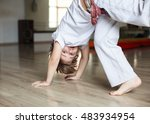 Small photo of Cute boy in white clothes practicing capoeira (brazilian martial art that combines elements of dance, acrobatics and music) in gym