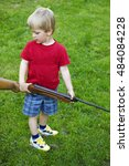 Small photo of Little child boy holding a real air gun,against green grass background.