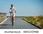 woman riding bike at seaside | Shutterstock . vector #484143988