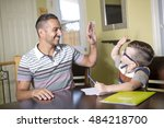 Small photo of A Father helping son do homework. Parent helps his child