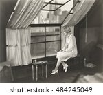 sad woman staring out window | Shutterstock . vector #484245049