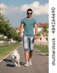 Stock photo young man and german spitz walk in the park he keeps the dog on the leash 484264690
