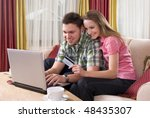 Happy couple using credit card shopping online with laptop computer at home - stock photo