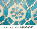 Small photo of Islamic star pattern architectural detail on fence in front of bright blue water background