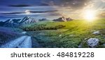 twenty four hour concept. composite summer landscape with high wild grass and purple flowers near the road to forest on mountain hillside and rocky peaks in the distance - stock photo