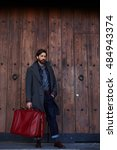 Small photo of Adult male dressed in fashionable spring clothes is posing outdoors against wooden background with copy space. Handsome bearded hipster man with stylish look is waiting taxi outside with travel bag