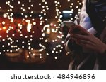 Cropped image of person booking hotel via smart phone application during vacation holidays in Christmas. Closely of a hipster girl is using her cell telephone, while is standing outdoors in night time - stock photo