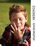 a young boy licks his fingers after eating lunch at a picnic - stock photo