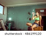 exhausted gym girl drinking... | Shutterstock . vector #486199120