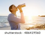 woman drinking water on beach | Shutterstock . vector #486419560