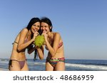 holiday fun: two young women drinking coconut water on the beach - stock photo