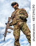 Small photo of Young handsome military man holding automatic rifle and hand grenade on sky background. Airsoft