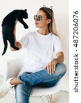 Stock photo woman wearing blanc t shirt jeans and sneakers sitting on chair and playing with black kitten 487206076
