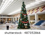 MOSCOW, RUSSIA - DEC 17, 2014: Security guard and other people walk in large hall with Christmas tree in Kremlin Palace.  - stock photo