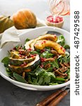 Small photo of Fall salad with greens, nuts, pomegranate seeds and roasted acorn squash