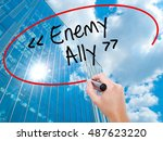 Small photo of Man Hand writing Enemy - Ally with black marker on visual screen. Business, technology, internet concept. Modern business skyscrapers background. Stock Photo