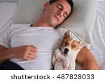 Stock photo man and dog sleeping together pet allergies concept 487828033