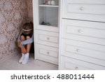 Small photo of Little aggrieved girl sitting in the corner of her room behind the cupboard