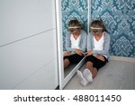 Small photo of Little aggrieved girl sitting in the corner of her room near the mirror, head down