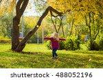 the girl runs under autumn tree | Shutterstock . vector #488052196