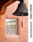 Small photo of Adobe Patio With Large Calling Bell And Window Reflecting Desert Landscape